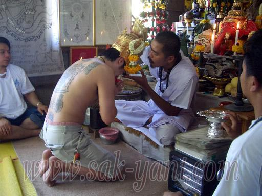 Ajarn Terng lays the Ruesi mask on the devotees head